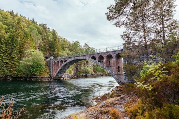 Oude voetbrug over de rivier dichtbij alesund; noorwegen