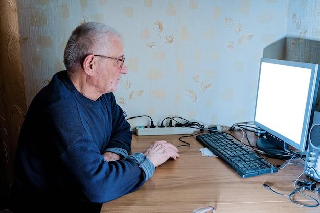 Oude volwassen man 80s thuis met behulp van pc. online pensioen, onderwijs, winkelen, medicijnen voor ouderen