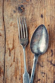 Oude vork en lepel op houten tafel