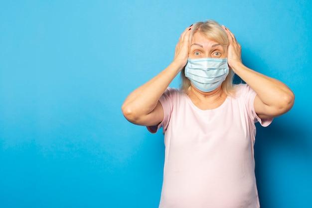Oude vriendelijke vrouw in een medisch beschermend masker met haar handen op haar hoofd met verbaasd gezicht op blauwe muur. emotioneel gezicht. virus, quarantaine, pandemie. gebaar van angst, zorgen, shock