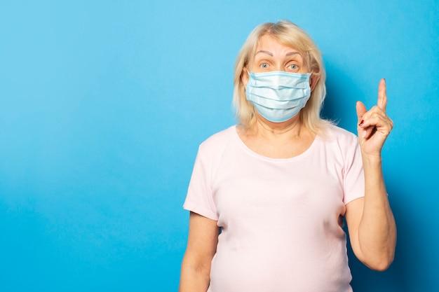 Oude vriendelijke vrouw in een medisch beschermend masker wijst haar vinger op blauwe muur. emotioneel gezicht. conceptvirus, quarantaine, vuile lucht, pandemie. gebaar wees voorzichtig, denk aan quarantaine