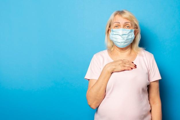 Oude vriendelijke vrouw in t-shirt en medische beschermend masker legde haar hand op haar borst tegen blauwe muur. emotioneel gezicht. conceptvirus, quarantaine, vuile lucht, pandemie. gebaar van angst, zorgen