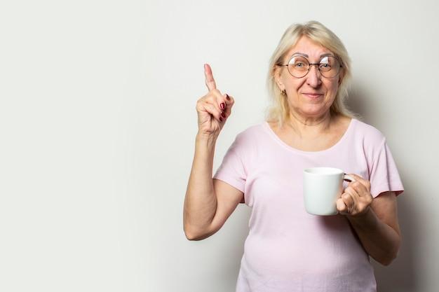 Oude vriendelijke vrouw met een glimlach in een casual t-shirt en een bril houdt een mok in haar handen en wijst met haar vinger op een geïsoleerde lichte muur. emotioneel gezicht. gebaar let op denk na