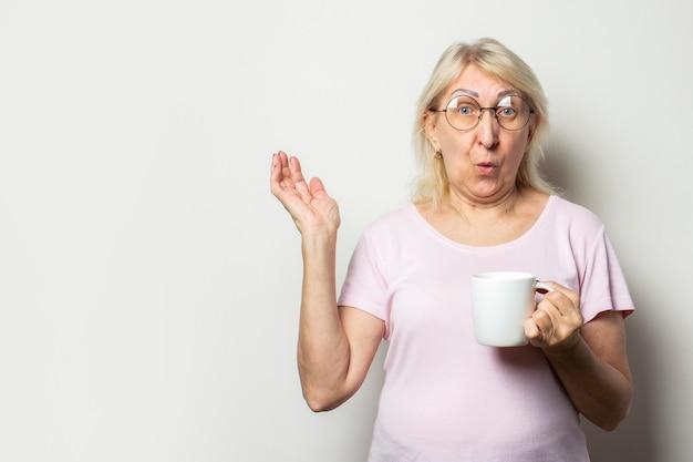 Oude vriendelijke vrouw met een verbaasd gezicht in een casual t-shirt en een bril met mok in zijn handen op geïsoleerde lichte muur. emotioneel gezicht. concept van koffie in de ochtend, ontbijt, verrassing, schok