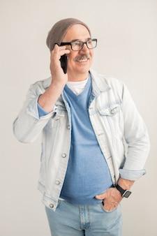 Oude vrolijke man in casual pullover, jasje, spijkerbroek en muts belt via smartphone terwijl hij bij een witte muur staat