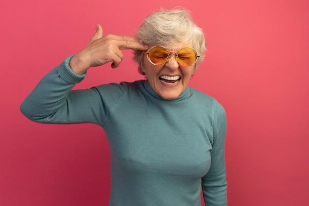 Oude vrouw beu met blauwe coltrui en zonnebril die zelfmoordgebaar doet met gesloten ogen geïsoleerd op roze muur met kopieerruimte