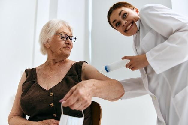 Oude vrouw bij de doktersafspraak grote spuit leuk