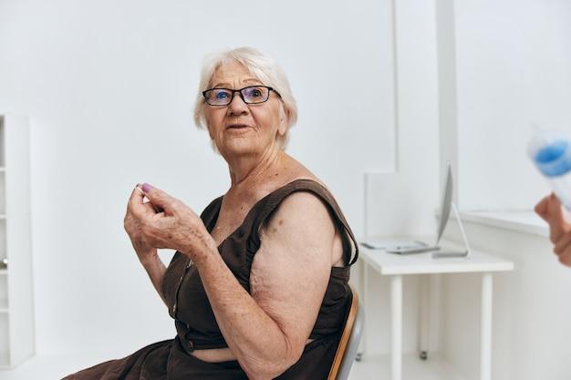 Oude vrouw bij de doktersafspraak spuit injectie plezier