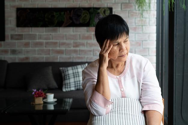 Oude vrouw die aan hoofdpijn, stress, migraine, gezondheidsprobleem lijdt