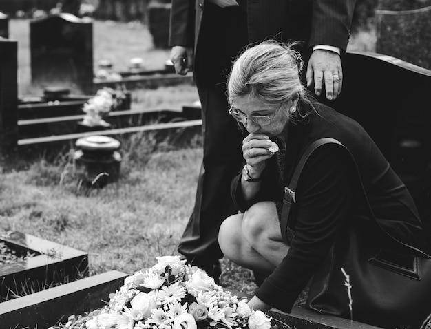 Oude vrouw die bloemen op een graf legt