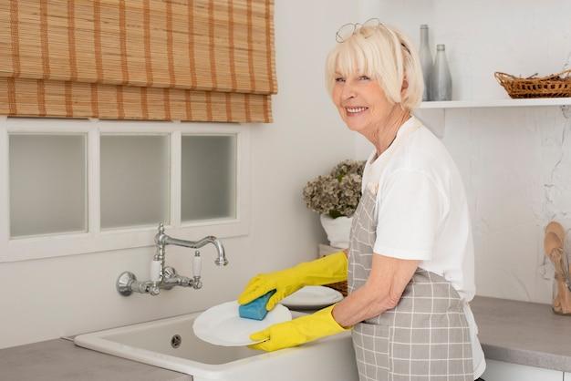 Oude vrouw die de schotels met handschoenen wast