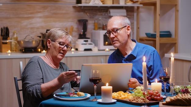 Oude vrouw die de vakantie online betaalt met laptop en kaart tijdens een romantisch diner. oude mensen zitten aan tafel, browsen, gebruiken de technologie, internet, vieren hun jubileum.