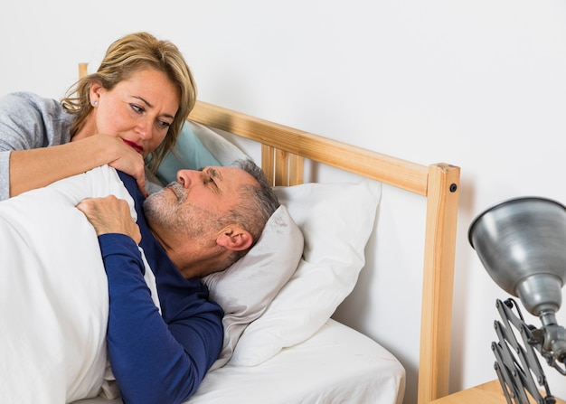 Oude vrouw die dichtbij de mens in dekbed op bed ligt