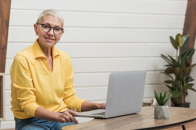 Oude vrouw die door internet op haar laptop kijkt