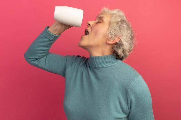 Oude vrouw die een blauwe coltrui draagt en een kopje thee vasthoudt