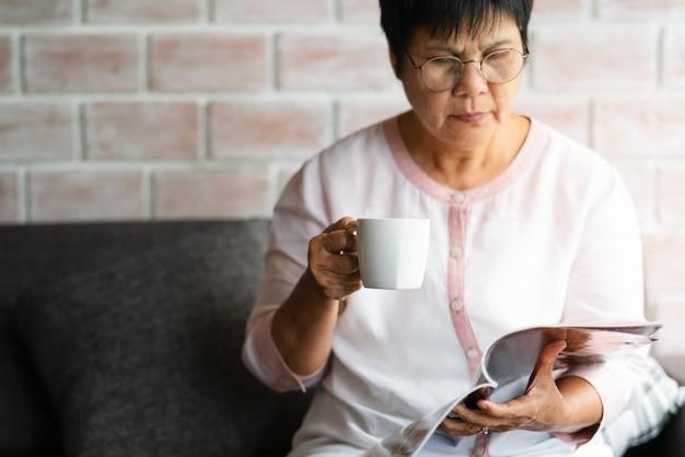 Oude vrouw die een boek met kop van koffie thuis leest