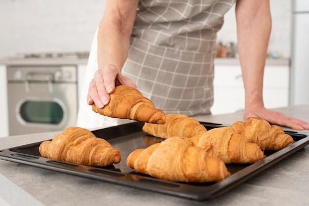 Oude vrouw die een croissant neemt uit het dienblad
