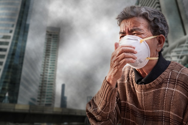 Oude vrouw die een de probleemluchtvervuiling van de maskervrees in de stad draagt