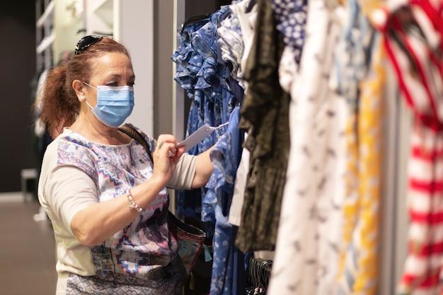 Oude vrouw die een gezichtsmasker draagt die een kleding in een kledingwinkel kijkt.