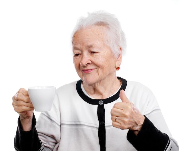 Oude vrouw die een kop van geïsoleerde koffie of thee proeft
