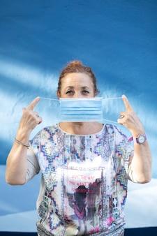 Oude vrouw die een medisch masker op haar gezicht zet.