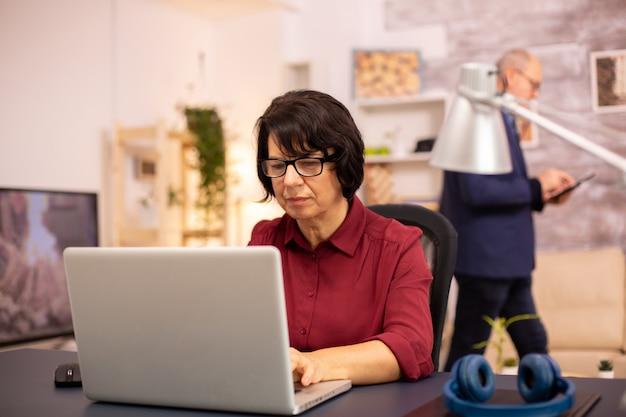 Oude vrouw die een moderne computer in haar woonkamer gebruikt terwijl haar man op de achtergrond loopt