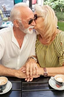 Oude vrouw die haar echtgenoot op de wang kust
