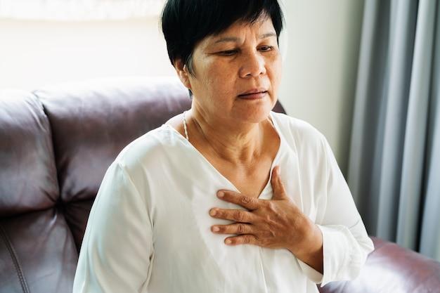 Oude vrouw die hartaanval heeft en haar borst grijpt