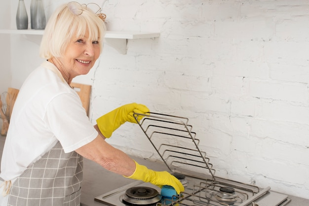 Oude vrouw die het fornuis met handschoenen wast