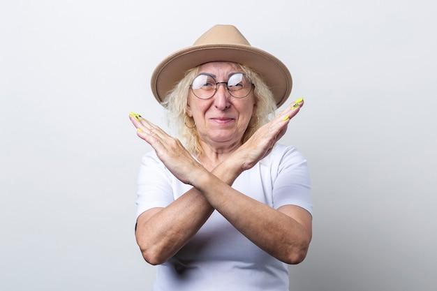 Oude vrouw die het teken van het stopverbod op lichte achtergrond toont.