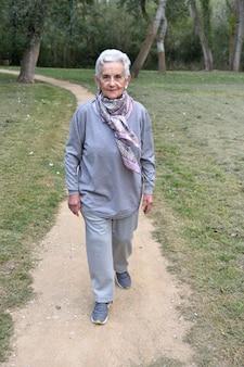 Oude vrouw die in een park loopt