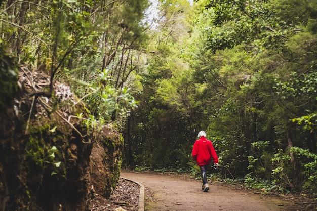 Oude vrouw die in het park loopt