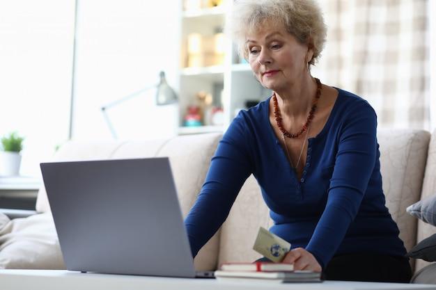 Oude vrouw die laptop met behulp van