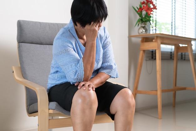 Oude vrouw die lijdt aan hoofdpijn, stress, migraine, gezondheidsprobleem concept