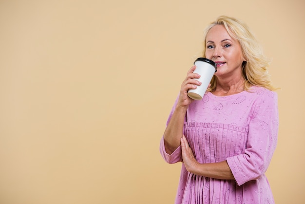 Oude vrouw die met kop van koffie de camera bekijkt