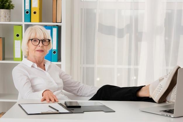 Oude vrouw die met oogglazen in haar bureau zit