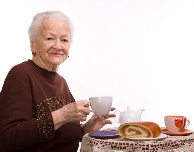 Oude vrouw die ontbijt op een wit heeft