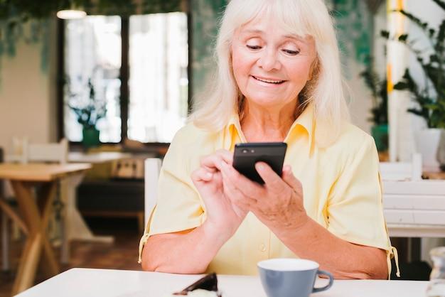 Oude vrouw die smartphone thuis gebruikt