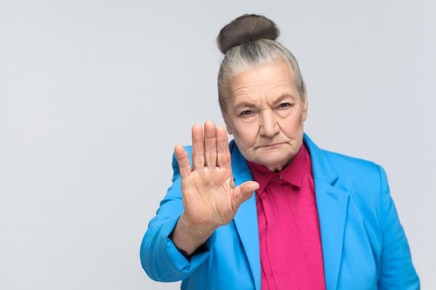 Oude vrouw die stopbord toont bij camera