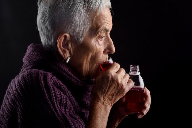 Oude vrouw die stroop neemt