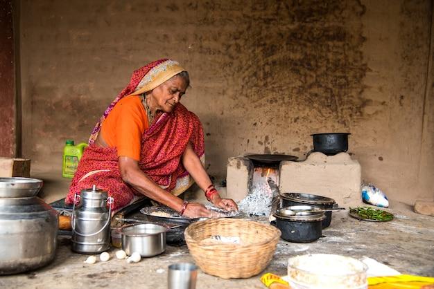 Oude vrouw die vers voedsel maakt en kookt in een landelijk dorp in een vintage keuken