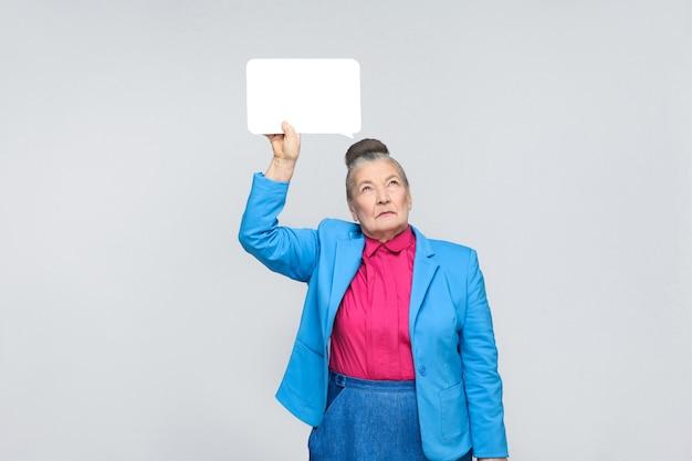 Oude vrouw die witte tablet vasthoudt en denkt