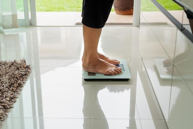 Oude vrouw die zich op gewichtsschaal bevindt in woonkamer