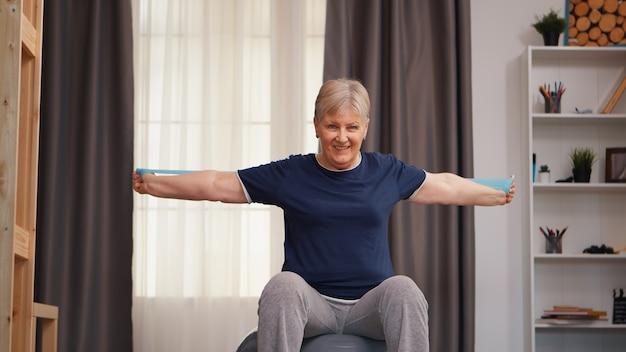 Oude vrouw doet fysieke training zittend op fitness bal. oude vrouw tillen opleiding gezonde levensstijl sport fitness workout thuis met gewichten halter activiteit