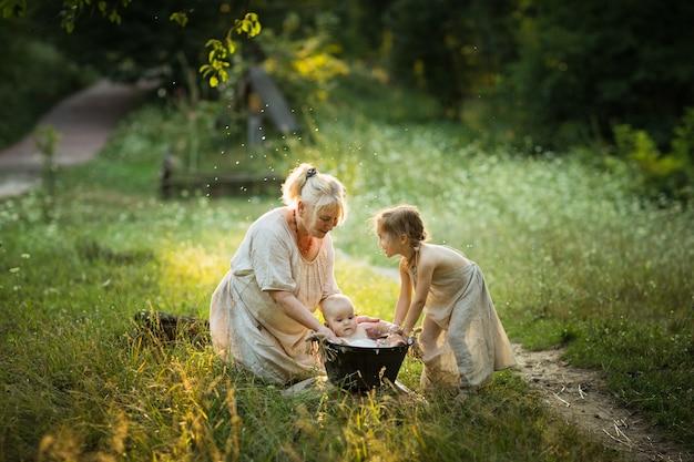Oude vrouw en meisje baden een baby in een bassin buiten