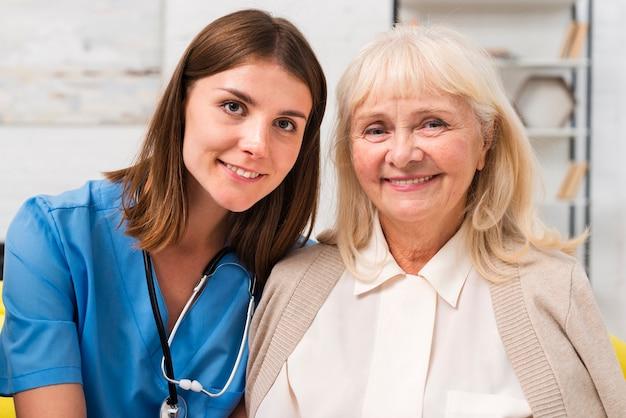 Oude vrouw en verpleegster die de camera bekijken