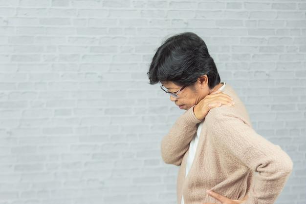 Oude vrouw gekwetst op de schouder op grijs