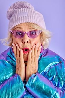 Oude vrouw hand in hand in de buurt van wangen met wijd open ogen en mond