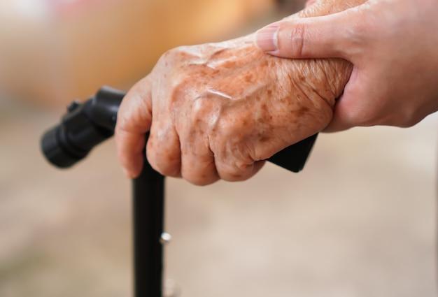 Oude vrouw hand met wandelstok ondersteund door dochter