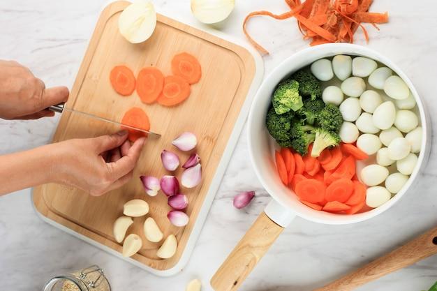 Oude vrouw handgekapte groente en wortel snijden op houten snijplank in de keuken. backstage maken koken. bovenaanzicht in witte houten tafel